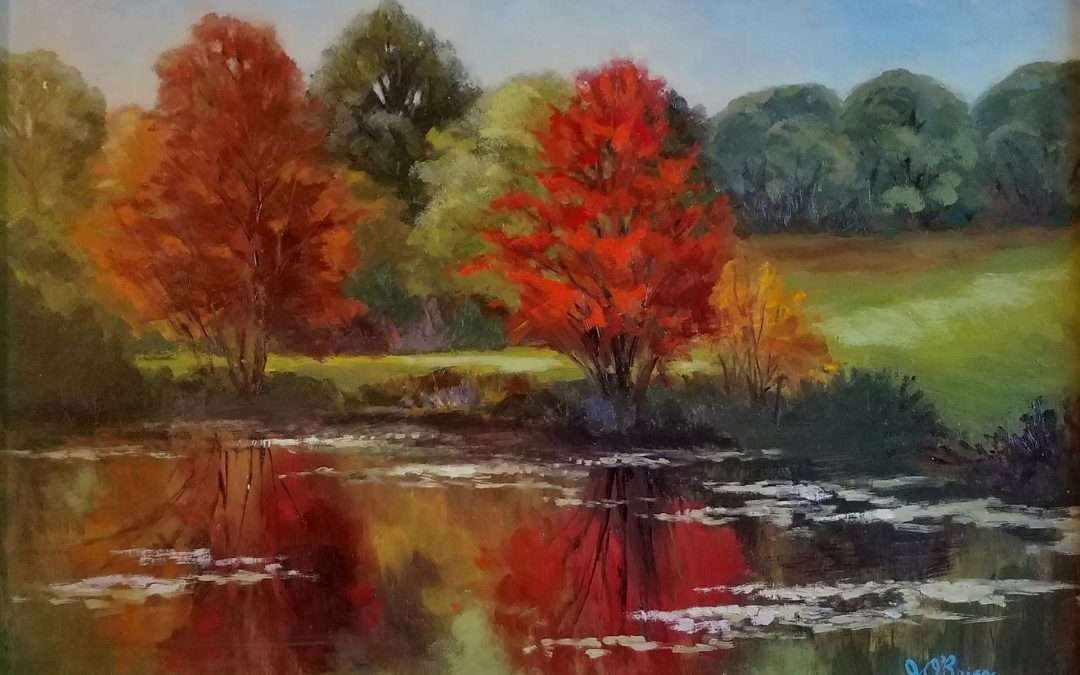 Plein air oil painting of fall foliage reflected in a pond with emphasis on complimentary color scheme. Painted on wood sided gator board. Oil by Jeanne Obrien