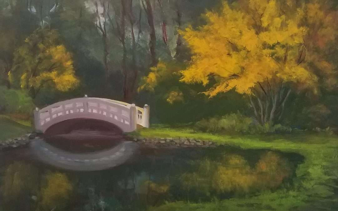 Plein air oil painting of the bridge at Wickham Park in Manchester CT. with fall foliage color reflected on the bridge and surrounding areas. Bridge is reflected on the pond along with fall foliage colors. Painted on wood sided gator board. Oil by Jeanne Obrien